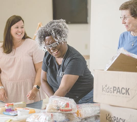 group of women packing food for kidspack